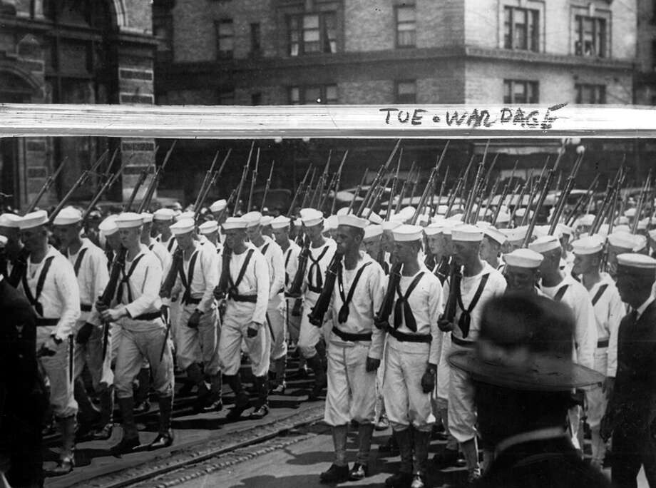"The caption for this photo read: ""Crowds cheering, bands blaring, flags flying, Naval cadets march down a Seattle street during wartime. Luckily these boys never learned in combat that war is not all cheering crowds, blaring bands, flying flags, but rather a ruthless struggle to kill, to live in the midst of death."" Photo: Seattlepi.com File"