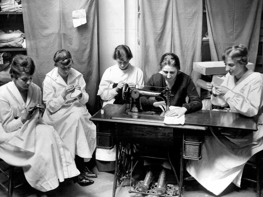 This photo that was published in the P-I May 31, 1918 shows Honor Guard members at theier Seattle headquarters making shirts and other items to send. Photo: Seattlepi.com File