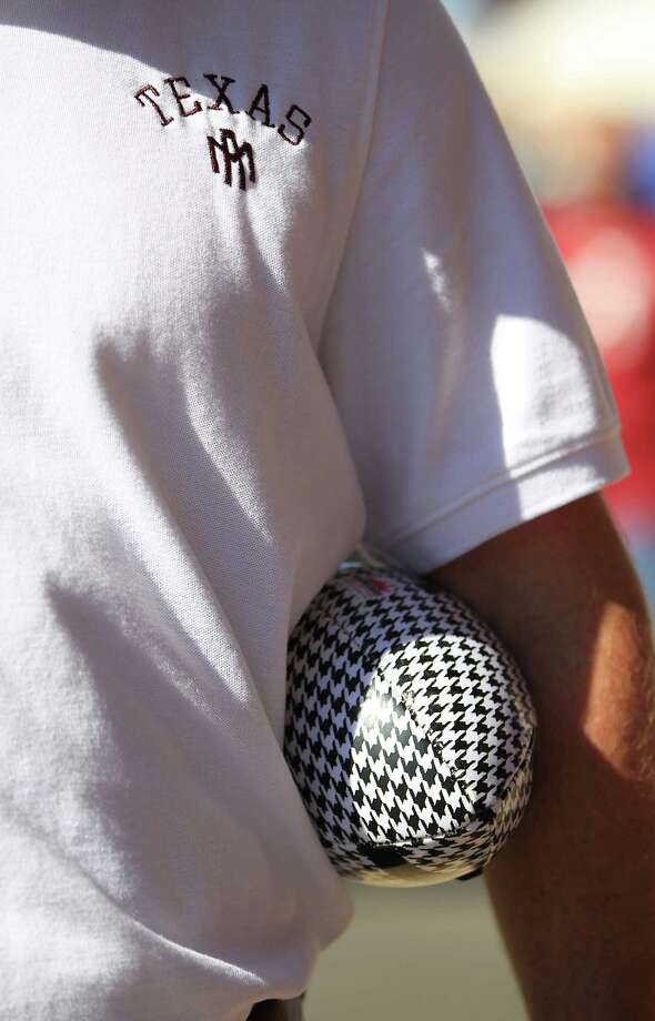 A Texas A&M fan holds a houndstooth patterned football before the start of a college football game at Bryant-Denny Stadium, Saturday, Nov. 10, 2012, in Tuscaloosa. Photo: Karen Warren, Houston Chronicle / © 2012  Houston Chronicle