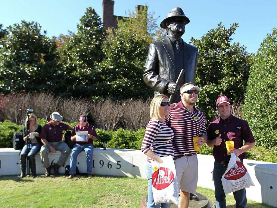 Texas A&M fans get their photos taken in front of the Bear Bryant statue before the start of a college football game at Bryant-Denny Stadium, Saturday, Nov. 10, 2012, in Tuscaloosa. Photo: Karen Warren, Houston Chronicle / © 2012  Houston Chronicle