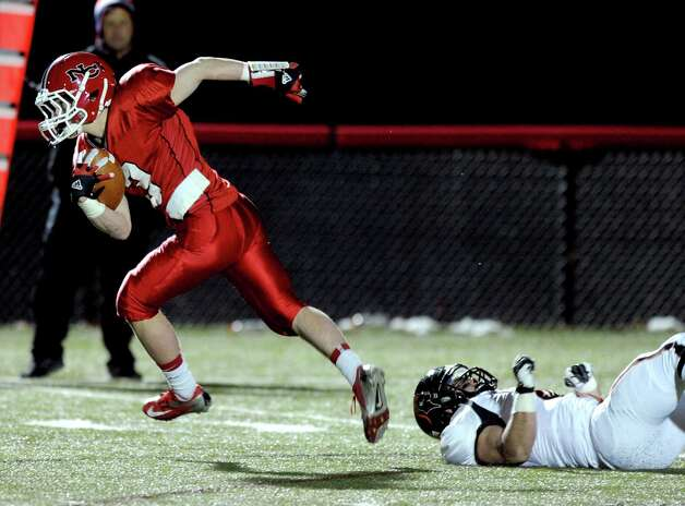 New Canaan's Jack Gilio carries the ball during Friday's football game against Stamford at New Canaan High School on November 9, 2012. Photo: Lindsay Niegelberg / Stamford Advocate