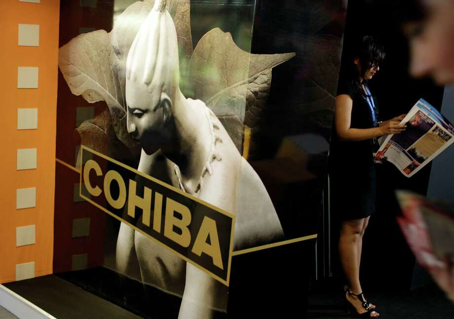 In this picture taken Monday Nov. 5, 2012  a woman reads a newspaper next to the stand of Cohiba during the 30th Havana International Fair in Havana, Cuba. Many of America's best-known brands were on display at a Havana exposition center this past week as representatives hawked some of the few U.S. products that can legally be exported to Cuba, thanks to an exception to the U.S. embargo allowing cash-up-front sales of food, agricultural goods and medicine.(AP Photo/Franklin Reyes) Photo: Franklin Reyes