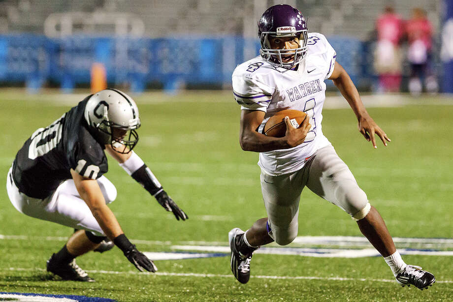 Warren's Aedric Robinson (right) races past Clark's Samuel Carter during the third quarter of their game at Farris Stadium on Nov. 9, 2012.  Clark claimed a spot in the playoffs with a 27-26 overtime victory over the Warriors.  MARVIN PFEIFFER/ mpfeiffer@express-news.net Photo: MARVIN PFEIFFER, Express-News / Express-News 2012