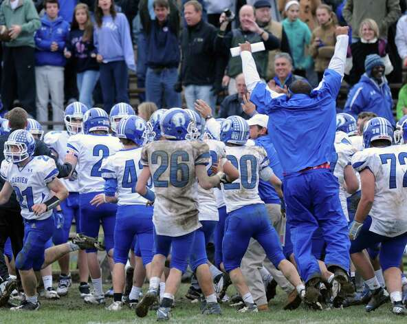 Darien players and coaches react after scoring a touchdown to break the tie during Saturday's football game at Trinity Catholic High School on November 10, 2012. Photo: Lindsay Niegelberg / Stamford Advocate
