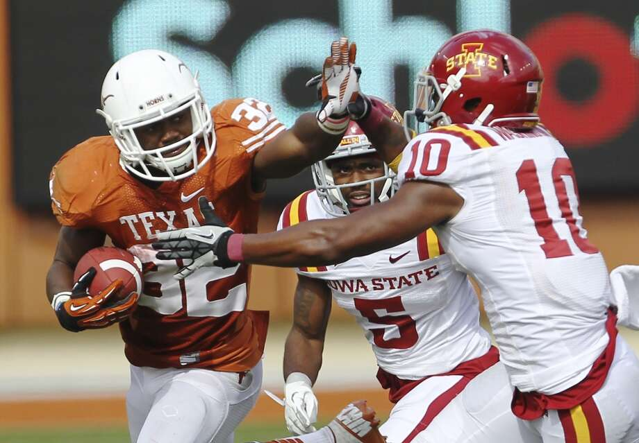Texas Longhorns' Johnathan Gray (32) fends off a tackle from Iowa State's Jacques Washington (10) in the second half at Darrell K. Royal Stadium in Austin on Saturday, Nov. 10, 2012. Texas defeated Iowa State, 33-7. (Kin Man Hui / San Antonio Express-News)