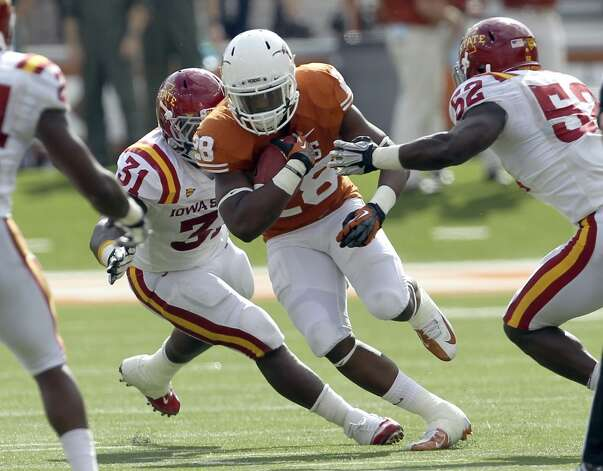 Texas Longhorns' Malcolm Brown (28) runs between Iowa State's Rony Nelson (31) and Jeremiah George (52) in the second half at Darrell K. Royal Stadium in Austin on Saturday, Nov. 10, 2012. Texas defeated Iowa State, 33-7. (Kin Man Hui / San Antonio Express-News)