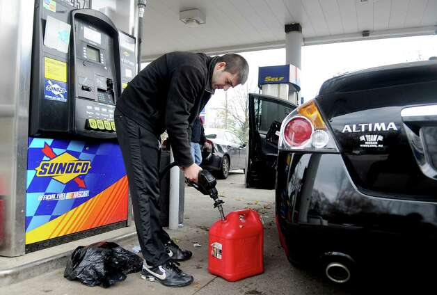 Andy Nekta fills a container with gas at a Sunoco station in Greenwich on Saturday, November 10, 2012. Nekta came from the Bronx to fill up in Connecticut because he has a delivery business and has to fill up every day. He said the extra gas in the container is for friends in New York. Photo: Lindsay Niegelberg / Stamford Advocate