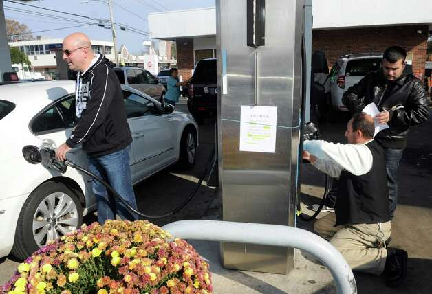 Long Island resident Ben Bongiovi fills his car with gas at the Gulf station on East Main Street off exit 9 on I-95 as the station dealer Ahmad Als puts up signs warning of fines if customers use illegal canisters for gas on Saturday, November 10, 2012. Photo: Lindsay Niegelberg / Stamford Advocate