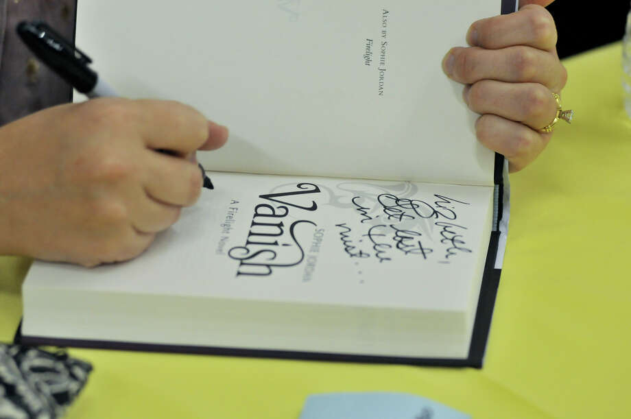 Author Sophie Jordan autographs copies of her book, Vanish, for children during the 9th annual San Antonio Express-News Children's Book Celebration Saturday at the Tripoint YMCA. Photo: Express-News