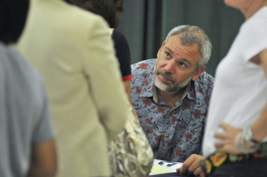 Author John Rocco autographs copies of his book, Blackout, for children during the 9th annual San Antonio Express-News Children's Book Celebration Saturday at the Tripoint YMCA. Photo: Express-News