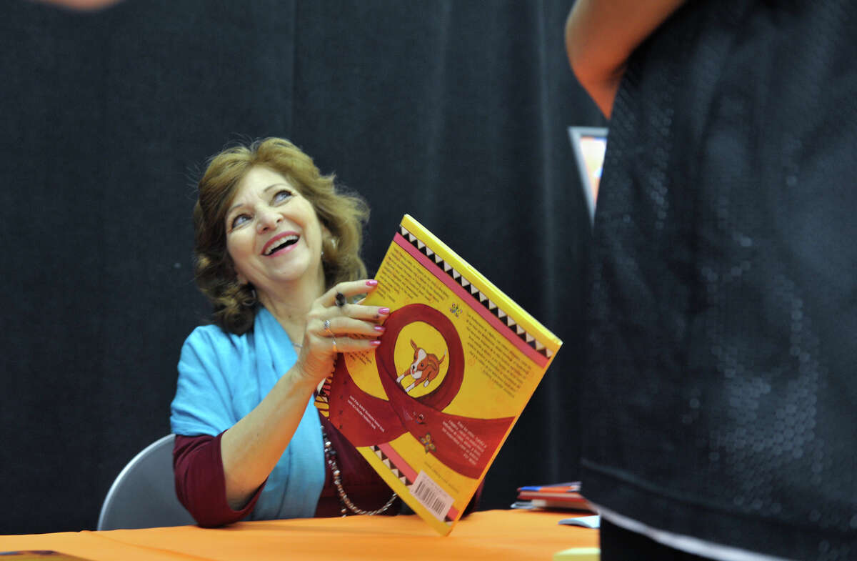 San Antonio author and Poet Laureat Carmen Tafolla laughs while signing a copy of her book, Rebozos, during the 9th annual San Antonio Express-News Children's Book Celebration Saturday at the Tripoint YMCA.