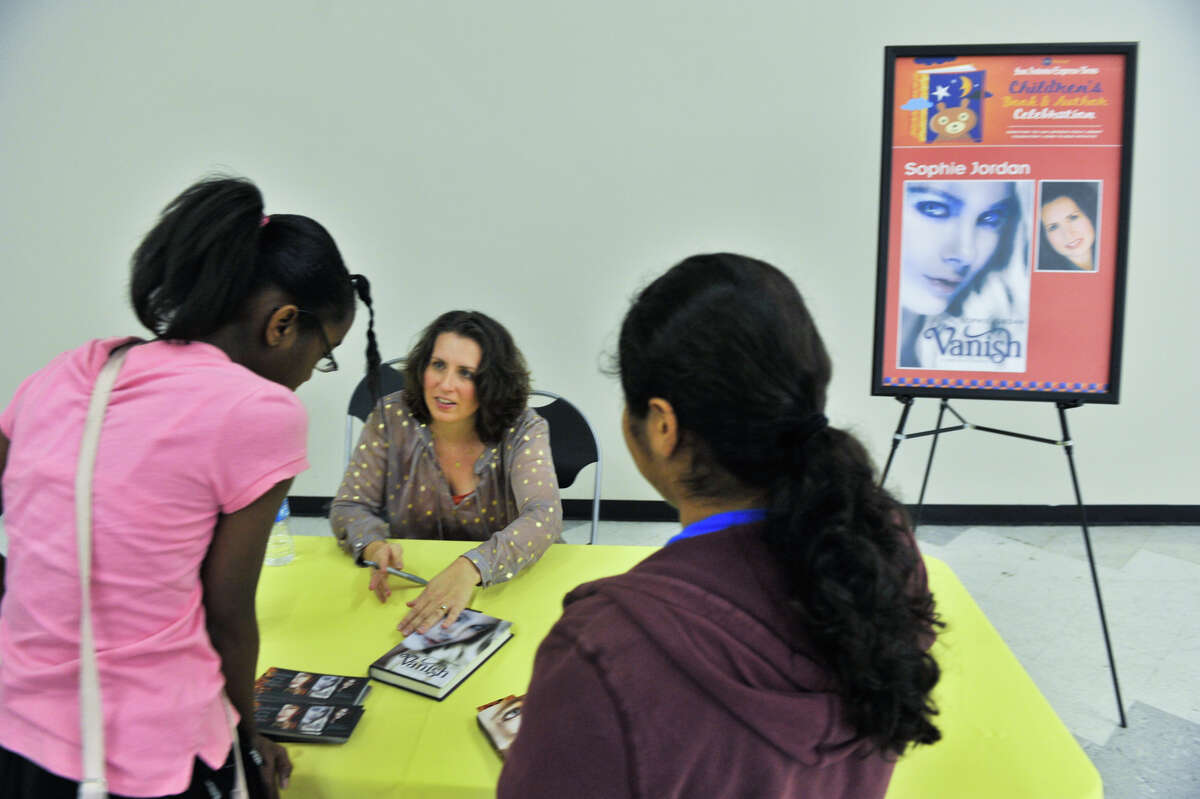 Author Sophie Jordan autographs copies of her book, Vanish, for Amber Kemper, 11, (left) and Raven Martinez (11) during the 9th annual San Antonio Express-News Children's Book Celebration Saturday at the Tripoint YMCA.