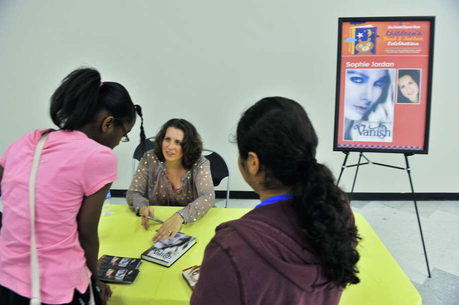 Author Sophie Jordan autographs copies of her book, Vanish, for Amber Kemper, 11, (left) and Raven Martinez (11) during the 9th annual San Antonio Express-News Children's Book Celebration Saturday at the Tripoint YMCA. Photo: Express-News