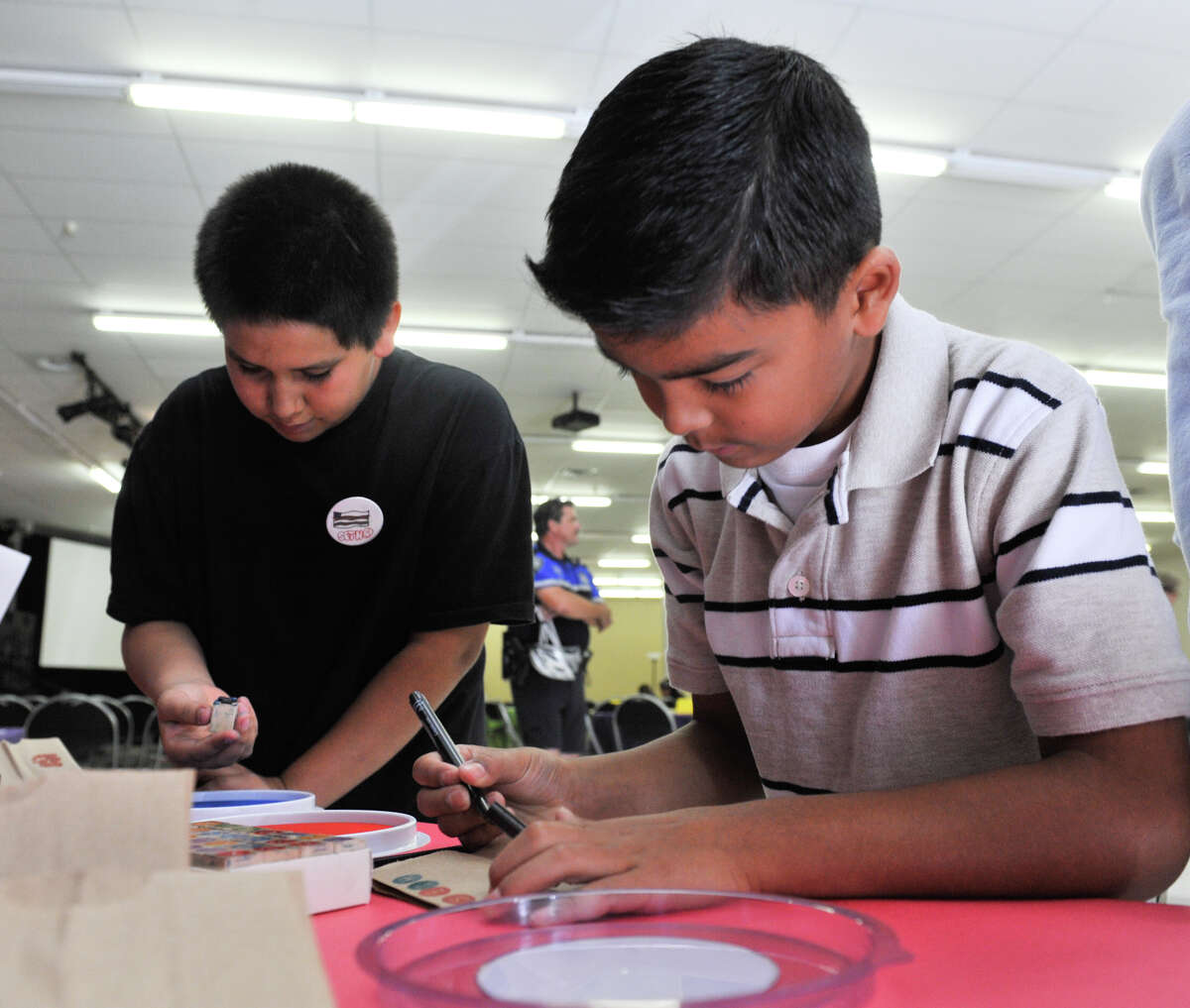 Seth Reynosa 13, (left) and Seth Martinez, 8, make their own books during the 9th Annual Express News Children's Book Celebration at the Tripoint YMCA Saturday.