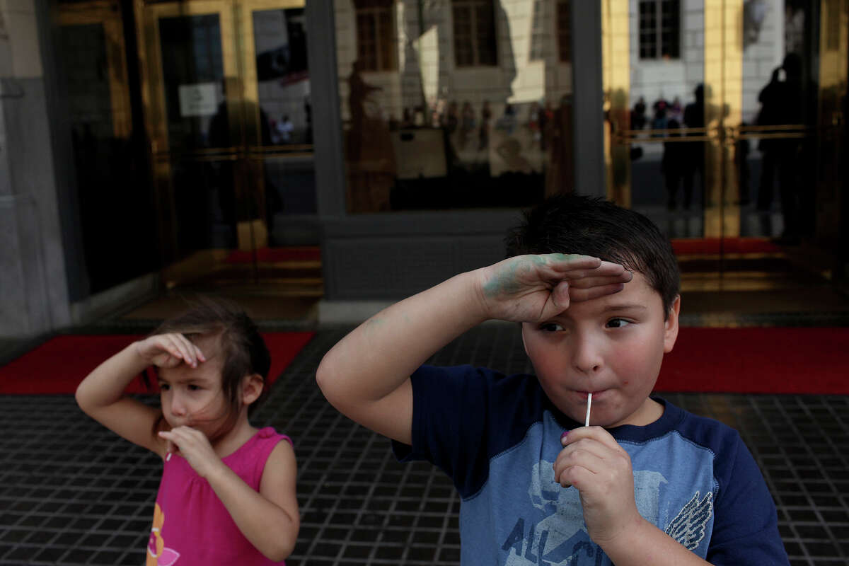 Daniel Vasquez, 7, and his cousin, Raven Borden, 4, salute as soldiers pass during the Veterans Parade in downtown San Antonio on Saturday, Nov. 10, 2012.