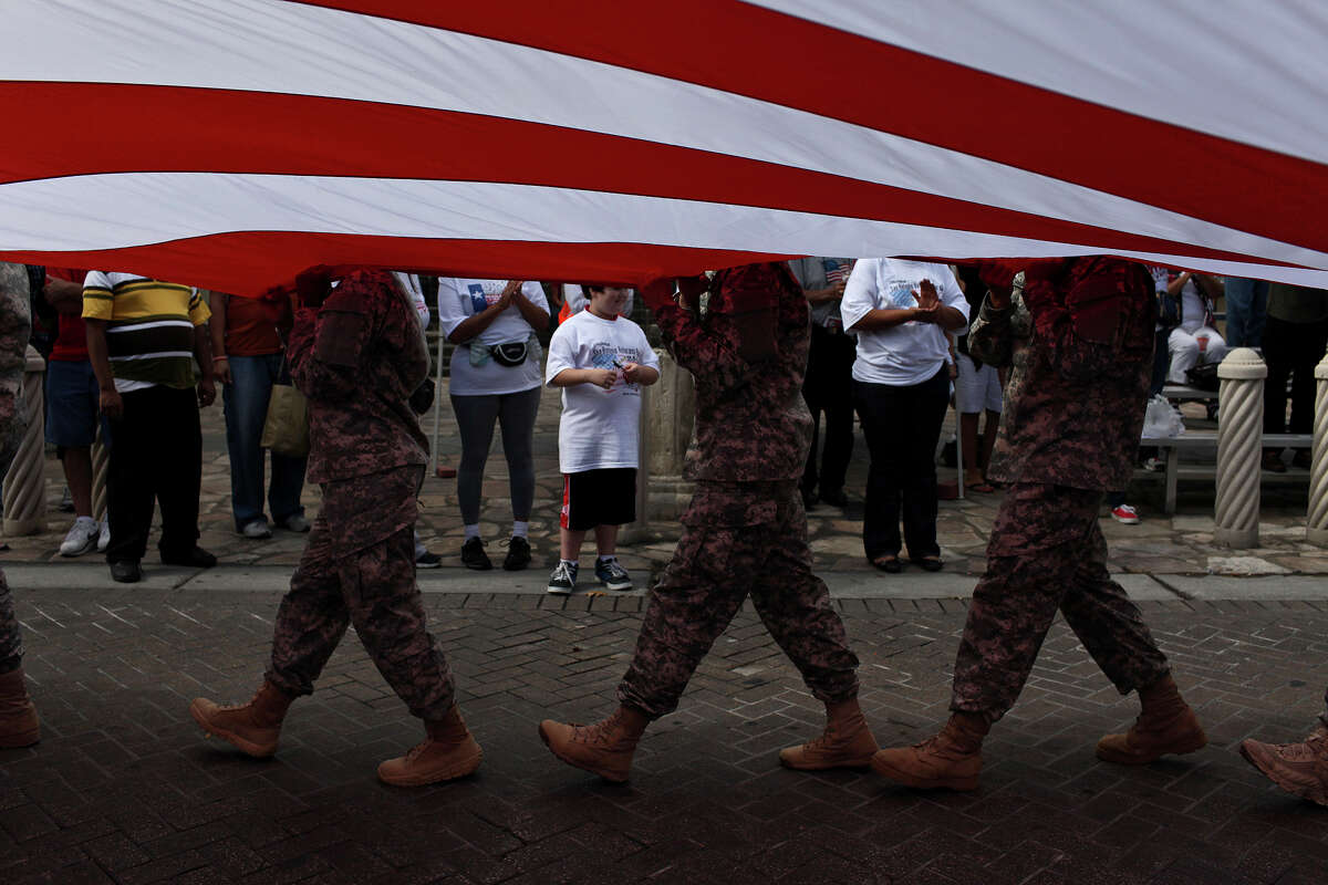 Soldiers with Charlie 187, 32nd Medical Brigade at Fort Sam Houston hold up a United States Flag as they participate in the Veterans Parade in downtown San Antonio on Saturday, Nov. 10, 2012.