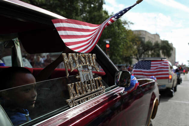 Gilbert Gonzalez, 8, waves a flag out the window of the car driven by his father, Ben Martinez, an Army veteran who served in Iraq, during the Veterans Parade in downtown San Antonio on Saturday, Nov. 10, 2012. Photo: Lisa Krantz, Express-News / © 2012 San Antonio Express-News