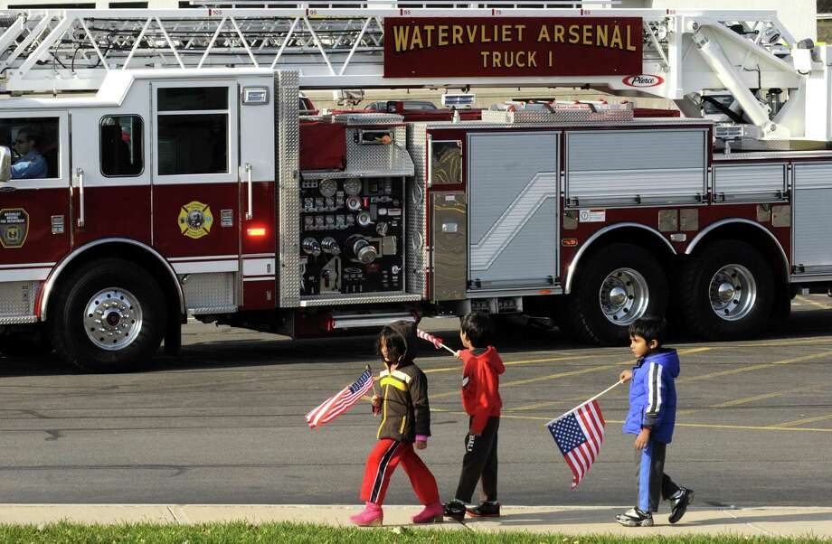 Children wave flags as the Watervliet Arsenal Truck One passes during the Menands Military Appreciation Parade and Picnic in Menands, NY Saturday Nov. 10, 2012. (Michael P. Farrell/Times Union) Photo: Michael P. Farrell