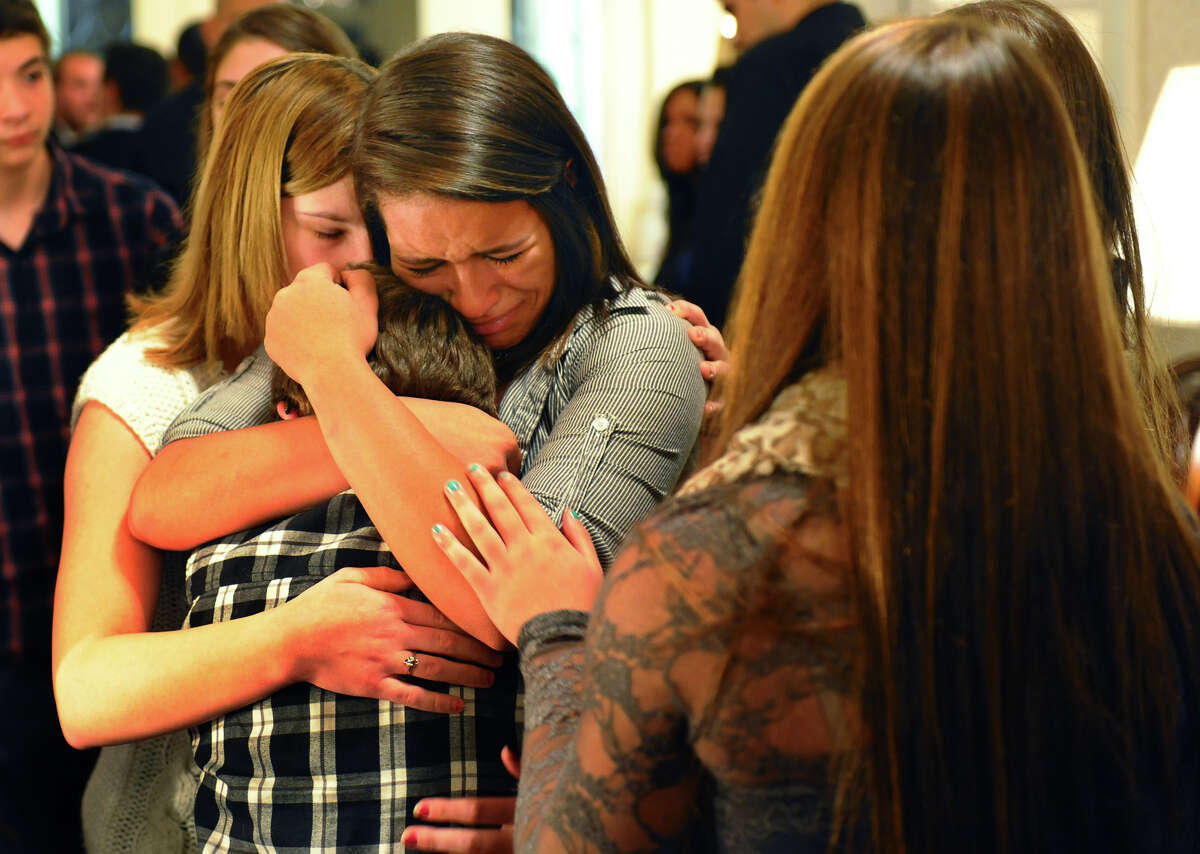 Billy Grzywacz, 11, is comforted by Jocelyn Grzywacz and Nicole Burr, at left, after a memorial service for their cousin Jet Krumwiede at Smith & Sefcik Funeral Home in Milford, Conn. on Saturday November 10, 2012. Krumwiede went missing in advance of Superstorm Sandy while kayaking with a friend.
