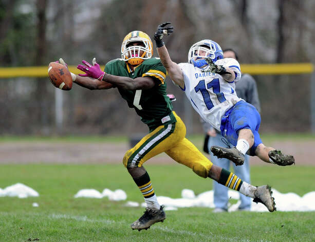 Trinity Catholic's Neno Merritt and Darien's Brian Wiegand reach for a ball that fell incomplete during Saturday's football game at Trinity Catholic High School on November 10, 2012. Photo: Lindsay Niegelberg / Stamford Advocate