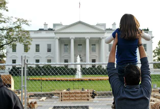 A tourist holds up his daughter to look at the White House as construction for US President Barack Obama's second inauguration is under way in Washington on November 10, 2012. Obama won Florida's 29 electoral votes in the presidential election on November 10, further fattening his substantial margin of victory in what had been predicted to be a close race. The state was the last to report its tally from the election November 6, in which Obama beat Republican Mitt Romney. With Florida's votes in the electoral college, the president's total goes up to 332, against 206 for Romney.  AFP PHOTO/Nicholas KAMMNICHOLAS KAMM/AFP/Getty Images Photo: NICHOLAS KAMM