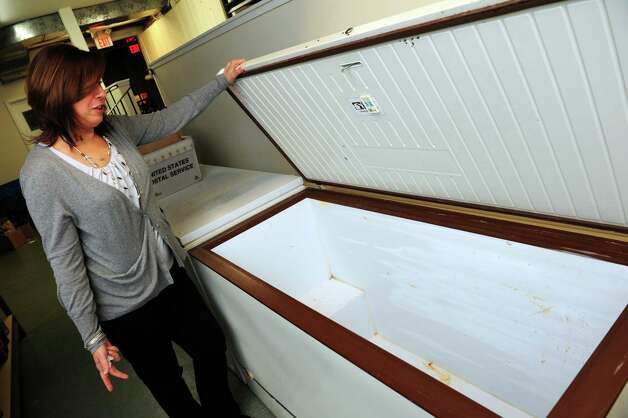 Carla Miklos, director of Operation Hope in Fairfield, opens a freezer at the food pantry Friday, Nov. 9, 2012 that was stocked with turkeys and chickens prior to Hurricane Sandy.  The organization was forced to throw out most of their perishables because of the power loss following the storm. Photo: Autumn Driscoll / Connecticut Post