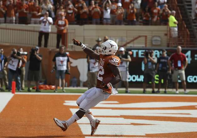 Texas Longhorns' Johnathan Gray (32) flashes the Longhorn sign after scoring a touchdown against Iowa State in the first half at Darrell K. Royal Stadium in Austin on Saturday, Nov. 10, 2012. (Kin Man Hui / San Antonio Express-News)