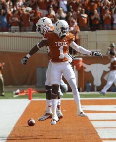 Texas Longhorns' Ashton Dorsey (85) celebrates Mike Davis' (01) 61-yard touchdown in the end zone during a game against Iowa State in the first half at Darrell K. Royal Stadium in Austin on Saturday, Nov. 10, 2012. (Kin Man Hui / San Antonio Express-News)