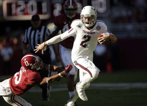 Texas A&M quarterback Johnny Manziel (2) runs through the tackle of Alabama defensive back Deion Belue (13) during the first half of an NCAA college football game at Bryant-Denny Stadium in Tuscaloosa, Ala., Saturday, Nov. 10, 2012. (AP Photo/Dave Martin) (Associated Press)