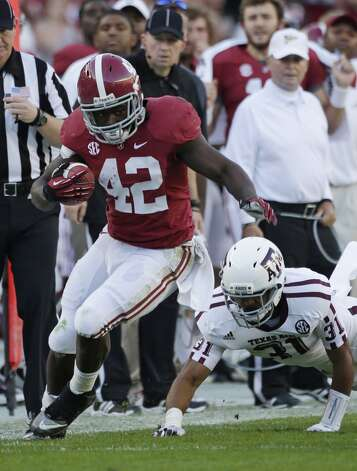 Alabama running back Eddie Lacy (42) runs out of the tackle of Texas A&M defensive back Howard Matthews (31) during the first half of an NCAA college football game at Bryant-Denny Stadium in Tuscaloosa, Ala., Saturday, Nov. 10, 2012. (AP Photo/Dave Martin) (Associated Press)