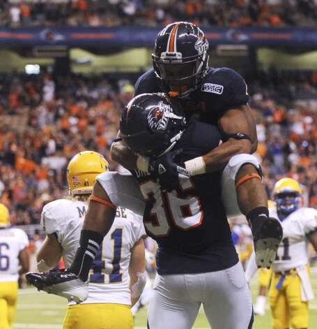 UTSA 31  - McNeese State 24: UTSA running back Evans Okotcha (36) celebrates with teammate David Glasco II after Okotcha scored a first-half touchdown against McNeese State in action at the Alamodome on Saturday, Nov. 10, 2012. (Billy Calzada / San Antonio Express-News)