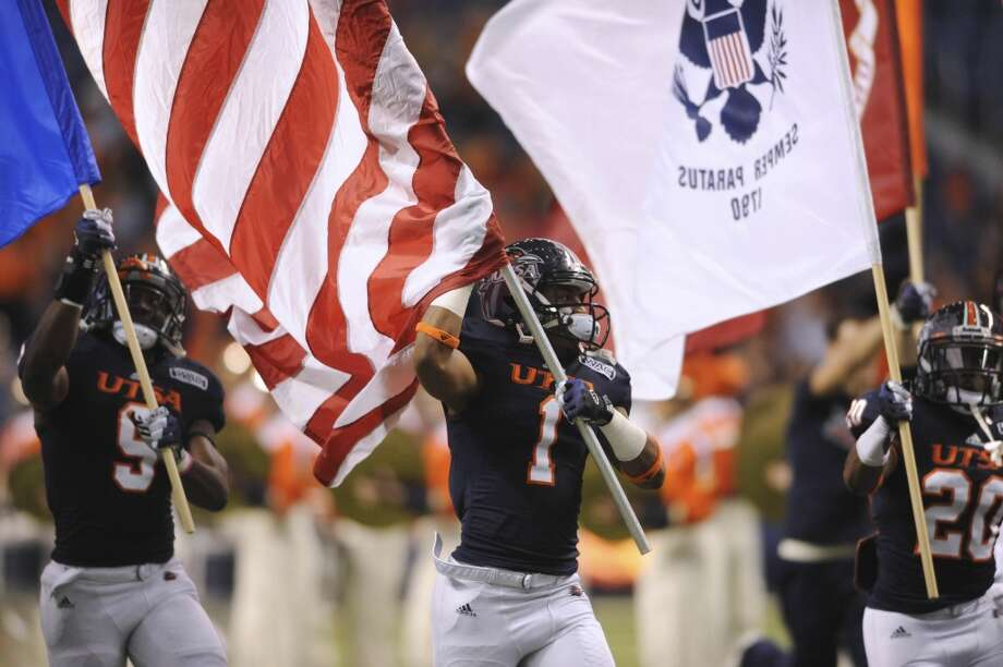 UTSA players Marcellus Mack (9), Kam Jones (1) and Maurice Paullard carry the national colors and the flags of the armed forces before their college football game against McNeese State in the Alamodome on Saturday, Nov. 10, 2012. (Billy Calzada / San Antonio Express-News)