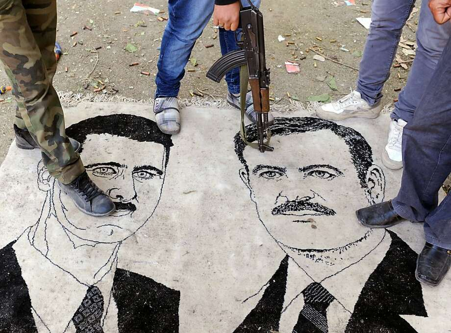 Syrian rebels stand on a mat depicting President Bashar al-Assad and his father, Hafez Assad. The Syrian National Council is trying to form a cohesive leadership. Photo: Bulent Kilic, AFP/Getty Images