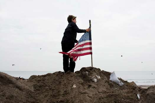 Matt Daly, 12, of Connecticut, places a U.S. flag atop a pile of sand removed from streets in the Rockaways, Saturday, Nov. 10, 2012, in the Queens borough of New York. Despite power returning to many neighborhoods in the metropolitan area after Superstorm Sandy crashed into the Eastern Seaboard, many residents of the Rockaways continue to live without power and heat due to damage caused by Superstorm Sandy. Photo: John Minchillo, Associated Press / FR170537 AP