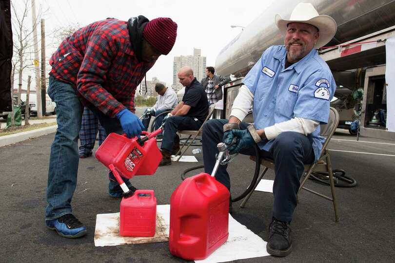 Brian Runestad, 44, a volunteer with Fuel Relief Fund, fills up gas cans for free in the Far Rockawa