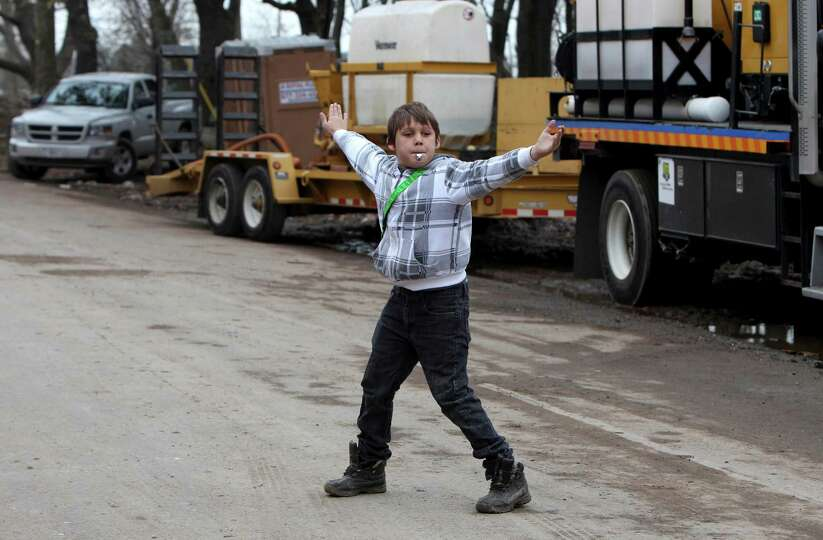 John Papanier, 12, directs traffic on a street congested by vehicles trying to help with the cleanup