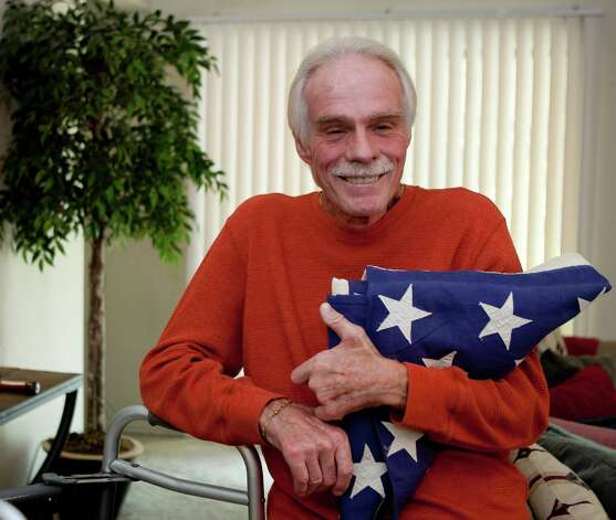 Robert Rountree poses Tuesday Nov. 6, 2012 with an American flag he bought about 20 years ago from a man who said it had draped his brother's coffin after he was killed in Vietnam. Photo: William Luther, San Antonio Express-News / © 2012 San Antonio Express-News