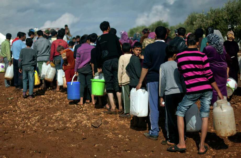 Syrians who fled from the violence in their village, carry plastic containers as they line up to fill them with water at a displaced camp, in the Syrian village of Atma, near the Turkish border with Syria. Saturday, Nov. 10, 2012. (AP Photo/ Khalil Hamra) Photo: Khalil Hamra, STF / AP