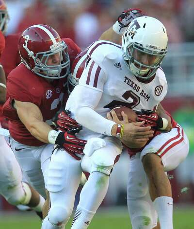 Texas A&M quarterback Johnny Manziel (2) is tackled by Alabama defensive back Vinnie Sunseri (3) during the first quarter of a college football game at Bryant-Denny Stadium, Saturday, Nov. 10, 2012, in Tuscaloosa. Photo: Karen Warren, Houston Chronicle / © 2012  Houston Chronicle
