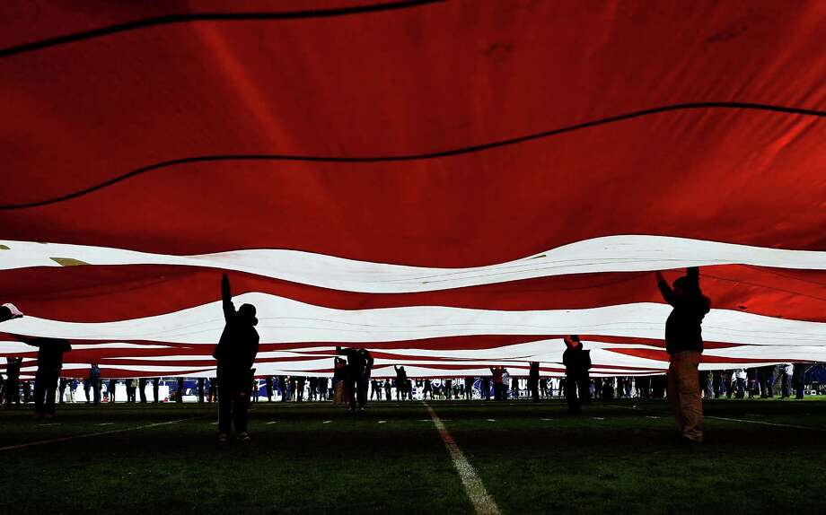 Volunteers hold up a giant American flag on the field prior to the game between the University of Connecticut Huskies and the University of Pittsburgh Panthers  on November 9, 2012 at Rentschler Field in East Hartford, Connecticut. Photo: Jared Wickerham, Getty Images / 2012 Getty Images