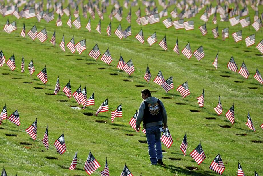 Jason Machado, of Fairhaven, Mass., walks among U.S. flags at the graves of deceased veterans at the National Cemetery in Bourne, Mass., Saturday, Nov. 10, 2012.  Hundreds of volunteers placed thousands of flags in the cemetery in advance of Veterans Day. Photo: Gretchen Ertl, Associated Press / FR170046 AP