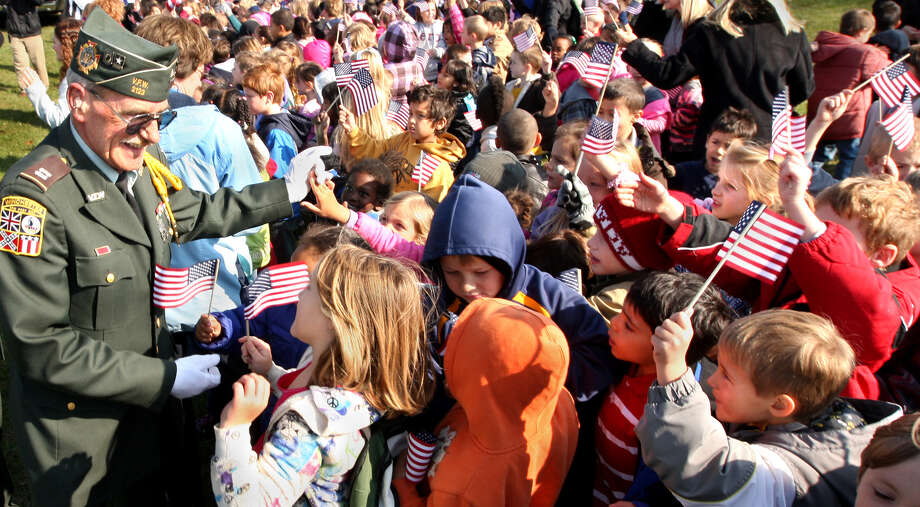 Korean War veteran Ed Ellis of Middletown, Va. is cheered and thanked for his service by hundreds of Red Bud Run Elementary School students at the conclusion of the 5th Annual Veteran's Day Celebration at Millbrook High School in Winchester, Va. Friday Nov. 9, 2012. Photo: Jeff Taylor, Associated Press / THE WINCHESTER STAR