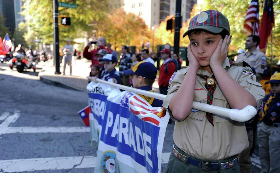 Cub Scout Ethan Jennings covers his ears as motorcycles roar by to start the 31st annual Veterans Day Parade through downtown Atlanta, Saturday, Nov. 10, 2012. Photo: David Tulis, Associated Press / FR170493 AP