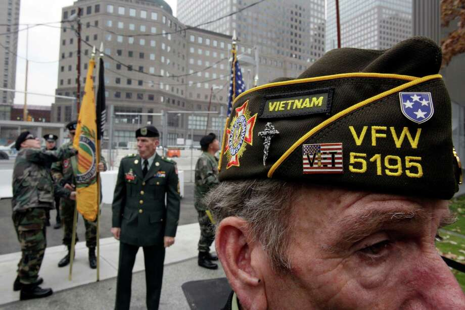 Jimmy Bacolo, right, of Staten Island, N.Y., a member of the Veterans of Foreign Wars 5195 in Red Hook, Brooklyn, N.Y., attends the Veterans Day observance at the 9/11 Memorial, in New York, Saturday, Nov. 10, 2012. On the eve of the Veterans Day parade, at the 9/11 Memorial at the World Trade Center,  a wreath was laid near the tree, which thrives more than a decade after it emerged from the smoking rubble. Photo: Richard Drew, Associated Press / AP