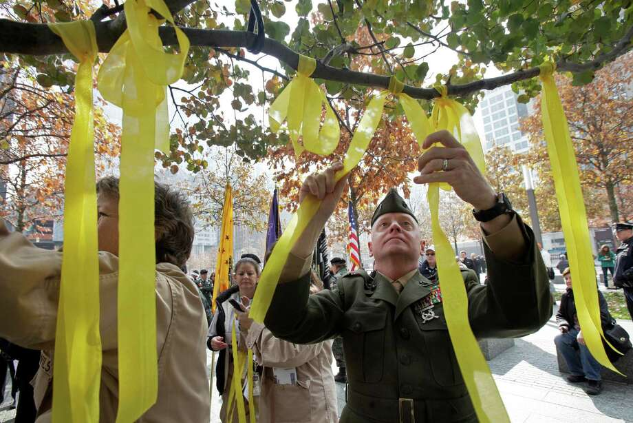 U.S. Marine Corps CWO4 Thomas Hoare, a 25-year veteran reservist, ties a yellow ribbon to the tree that survived the terror attack, during the Veterans Day observance at the 9/11 Memorial, in New York, Saturday, Nov. 10, 2012. On the eve of the Veterans Day parade, at the 9/11 Memorial at the World Trade Center,  a wreath was laid near the tree, which thrives more than a decade after it emerged from the smoking rubble. Photo: Richard Drew, Associated Press / AP