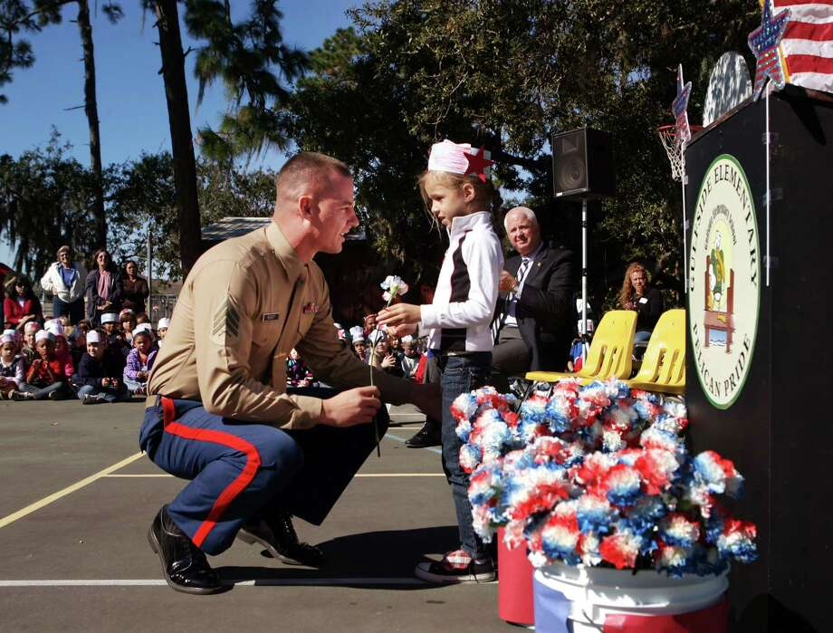 Active duty United States Marine, Sgt. Michael Reinert , of Holiday, receives a carnation Friday from his daughter, six-year-old Ariana Reinert, while attending Gulfside Elementary School's 14th-annual Veterans Day Celebration at the school in Holiday, Fla. Friday, Nov. 9, 2012. All 520 members of the student body, their families and the school's faculty gathered at the event where a list of local veterans were read who are currently serving or who have served in the United States military. The acknowledgements were accompanied by the gifting of carnations to the veterans and their family members accompanied by patriotic performances by the school's chorus. Photo: Douglas R. Clifford, Associated Press / Tampa Bay Times
