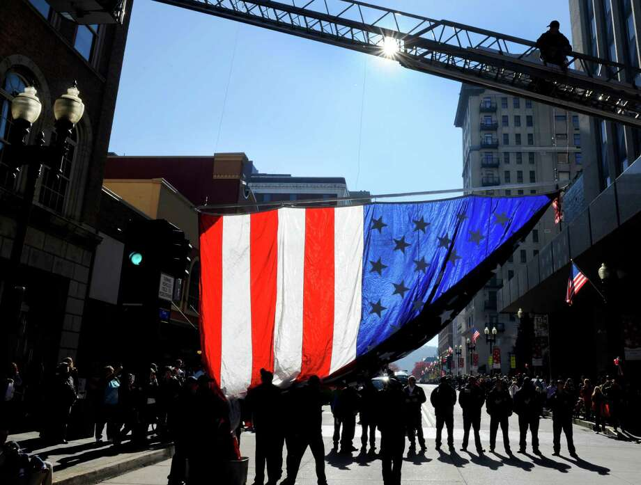 Members of the Knoxville Fire Department raise an American flag over Gay Street in Knoxville, Tenn., before the start of the city's 87th Veterans Day Parade on Friday, Nov. 9, 2012. Thousands lined up to watch the 90-minute parade. Photo: Michael Patrick, Associated Press / Knoxville News Sentinel