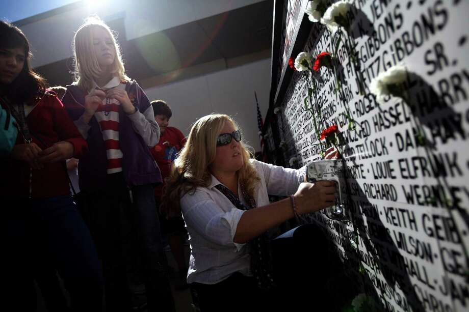 Shop teacher Jenna Jenkins staples students' carnations to the Wall of Remembrance during Palm Harbor Middle School's annual Veteran's Day celebration in the courtyard Friday morning, Nov. 9, 2012, in Palm Harbor, Fla. Friday marked the 28th anniversary of the school's Wall of Remembrance, where students and their families continue to add names of veterans to honor and remember. Photo: Vragovic, Will, Associated Press / Tampa Bay Times