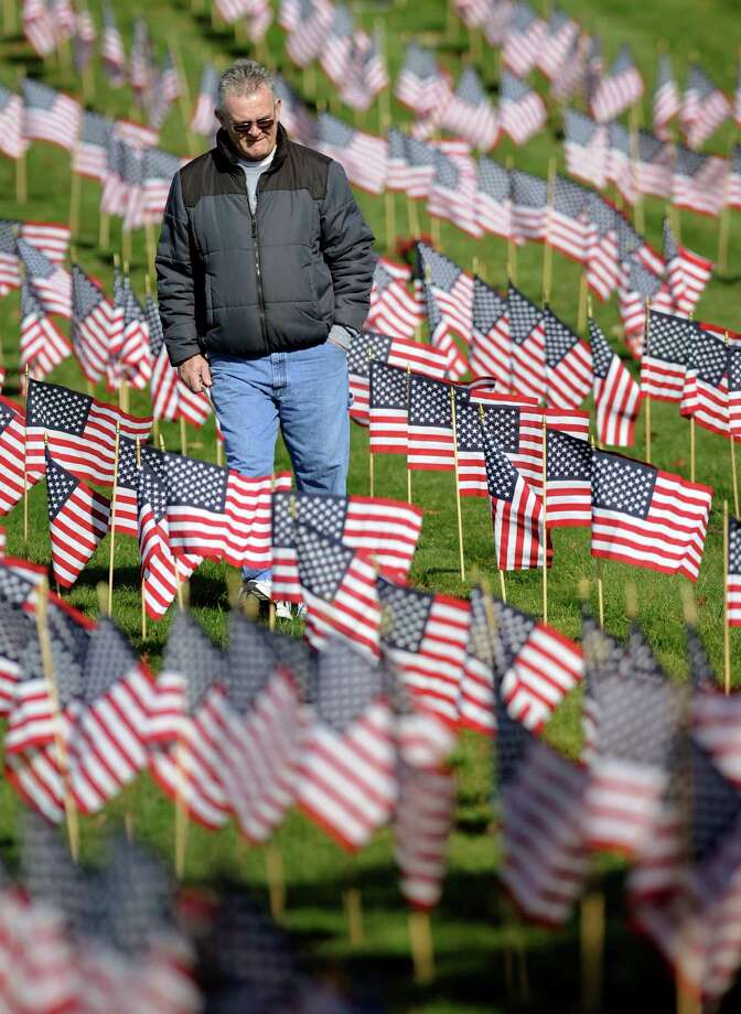 A volunteer walks among U.S. flags at the graves of deceased veterans at the National Cemetery in Bourne, Mass., Saturday, Nov. 10, 2012.  Hundreds of volunteers placed thousands of flags in the cemetery in advance of Veterans Day. Photo: Gretchen Ertl, Associated Press / FR170046 AP