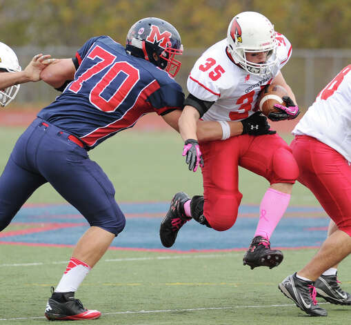 Runningback Mark Bernstein # 35 of Greenwich High School blasts through a hole as Brien McMahon's James Pace # 70 gets an arm on him during the football game between Brien McMahon and Greenwich at Brien McMahon High School in Norwalk, Saturday afternoon, Nov. 10, 2012. Photo: Bob Luckey / Greenwich Time